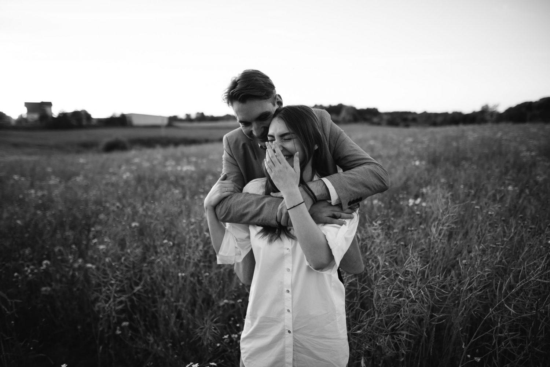 Poros fotosesija, Austėja ir Paulius apsikabinę nuoširdžiai juokiasi apšviesti saulėlydžio