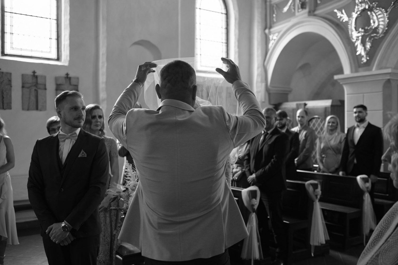 Jaunosios krikšto tėtis nuima Indrei veliumą vestuvių ceremonijos metu Kaune