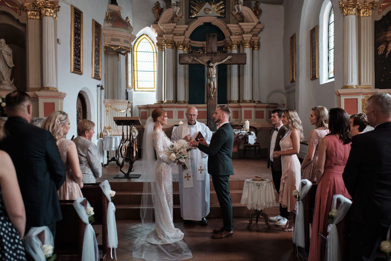 Jaunieji sako priesaiką ir apsikeičia žiedais bažnytinės ceremonijos metu