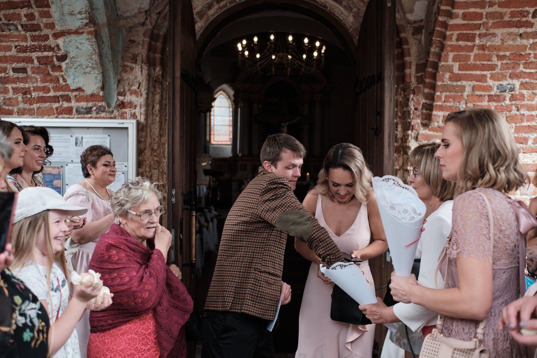 Svečiai ruošiasi sveikinti jaunuosius po ceremonijos, bažnyčios kiemelis