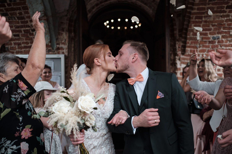 Jaunieji bučiuojasi bažnyčios kiemelyje po ceremonijos