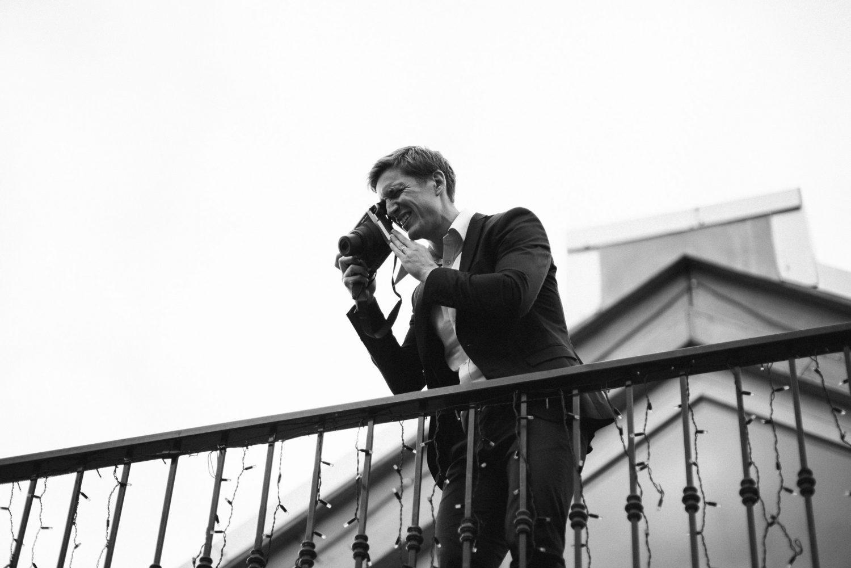 Jaunųjų draugas daro vestuvių svečių būrelio nuotrauką