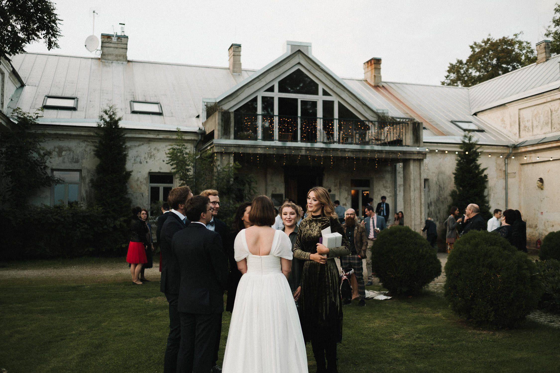 Vestuvių svečiai sveikina jaunuosius. Nuotraukos fone – žavusis Babtyno-Žemaitkiemio dvaras