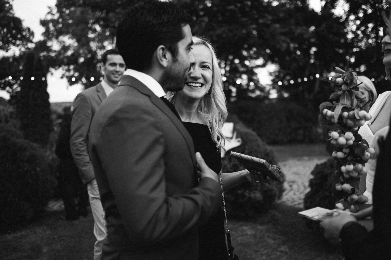 Vestuvių svečiai linksmai juokaudami sveikina jaunuosius