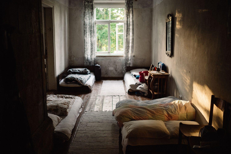 Romantiškas Jakiškių dvaro interjeras, apšviestas šiltos vakaro saulės. Svečių miegui paruoštas kambarys