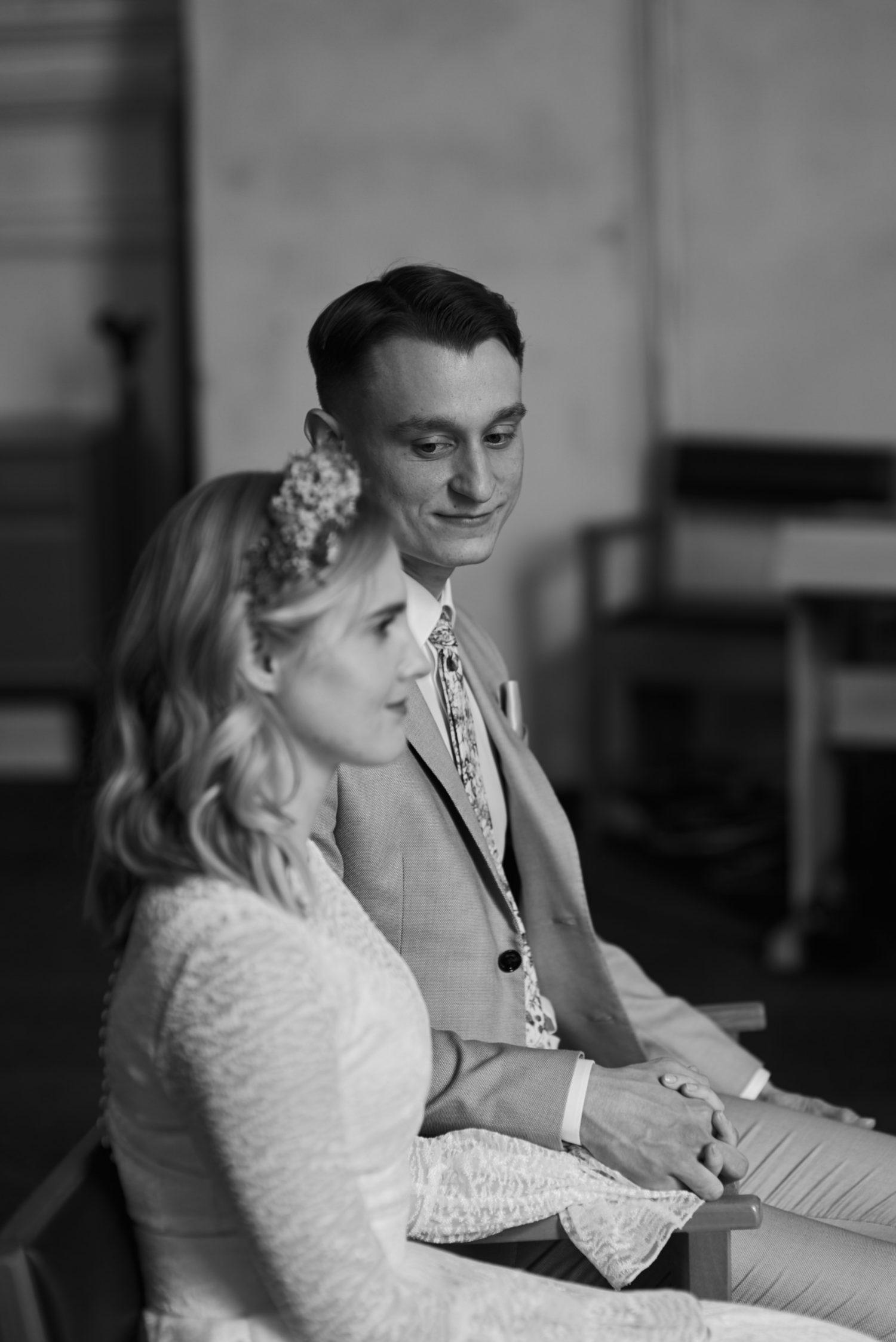 Milda ir Vilius sėdi priešais altorių bažnyčioje, ceremonija, juodai balta nuotrauka