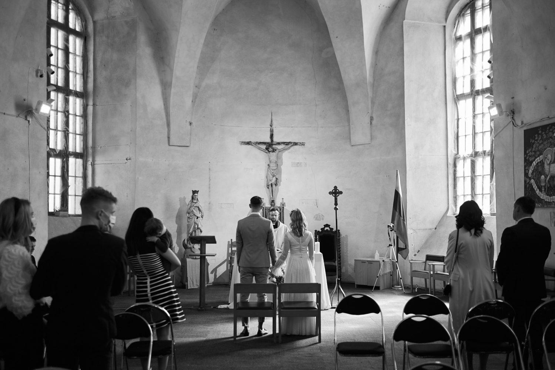 Ceremonija bažnyčioje, Milda ir Vilius stovi altoriaus fone, bendro plano juodai balta nuotrauka