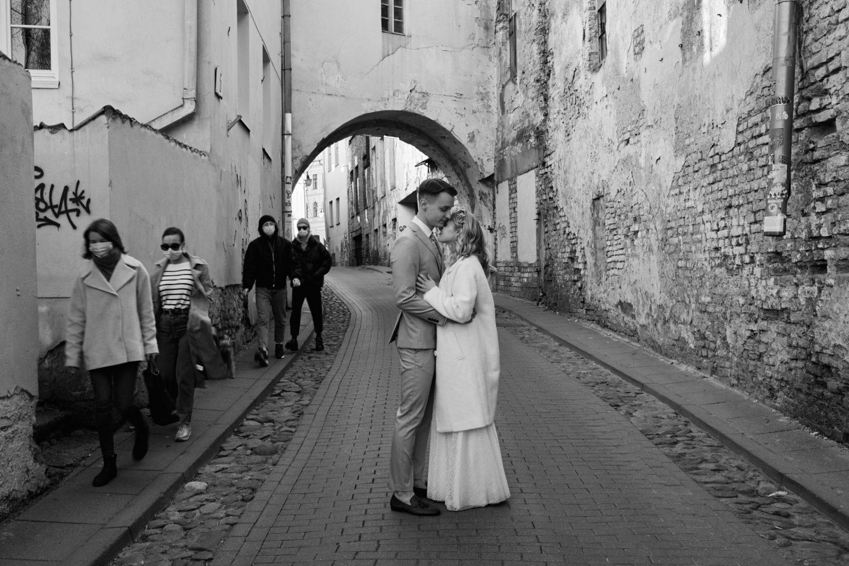 Bendro plano portretas, jaunieji apsikabinę Vilniaus senamiesčio gatvėje pro šalį einant žmonėms