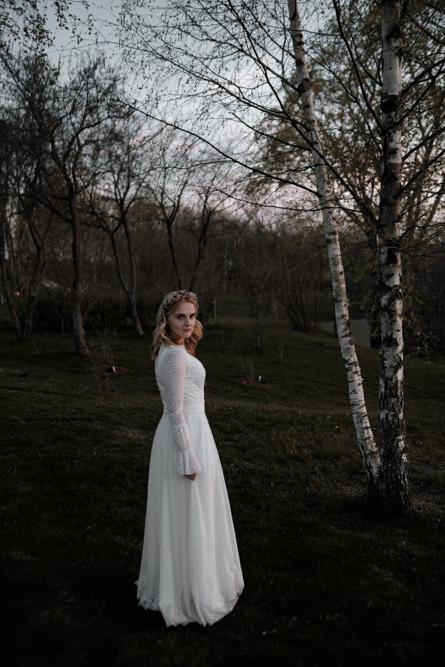 Vidutinio plano Mildos portretas vestuvių dienos vakare, tarp jaunų berželių