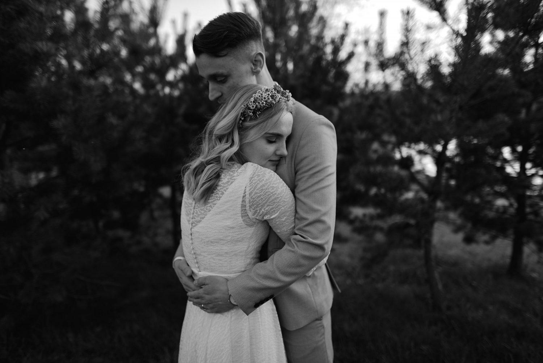 Juodai baltas apsikabinusių jaunųjų portretas vestuvių dienos vakarą