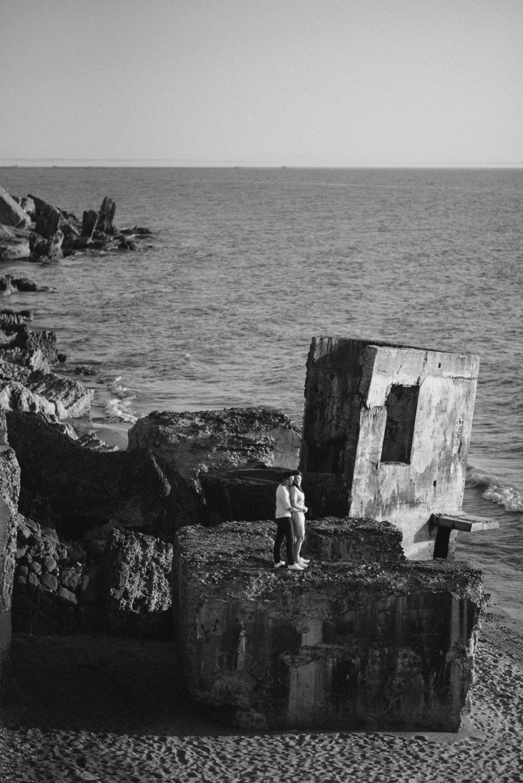 Poros fotosesija prie jūros – juodai baltas bendro plano poros portretas Latvijos pajūryje