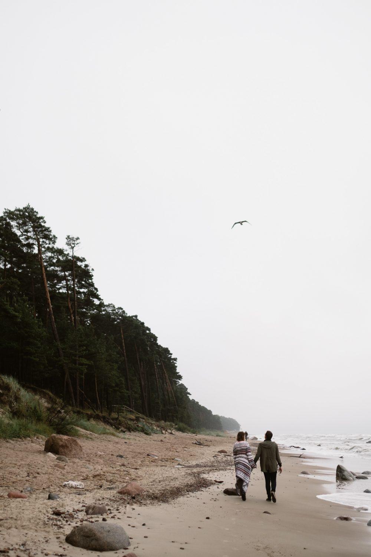 Priešvestuvinė fotosesija pajūryje, prie Baltijos. Jaunieji vaikštinėja smėlėtu krantu