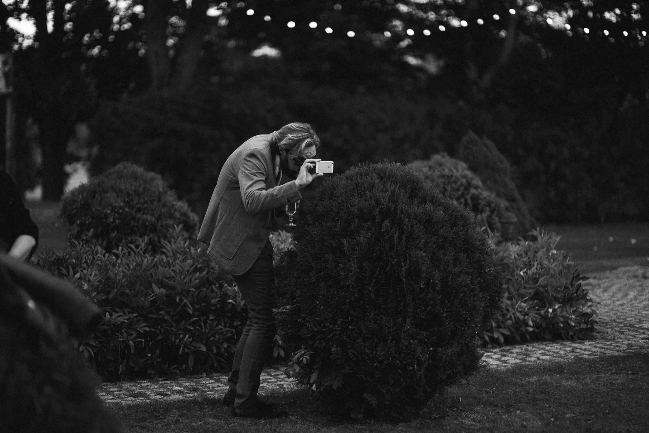 Vestuvių svečias, šiek tiek slapukaudamas, telefonu įamžina gražų vakarą Babtyno-Žemaitkiemio dvare