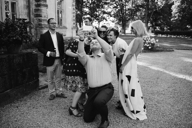 Laimingi vestuvių svečiai fotografuojasi Jakiškių dvaro kiemelyje